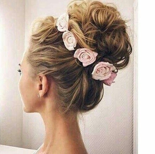 Voluminous High Bun Updo Made With Curls And Crowned With Flowers Within Most Recent Updo Hairstyles With Flowers (View 2 of 15)