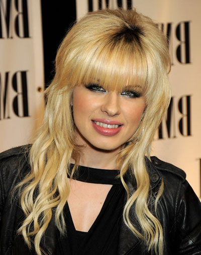 Orianthi's Voluminous Curly Half Up Hairstyle With Blunt Bangs pertaining to 2018 Voluminous Wavy Layered Hairstyles With Bangs