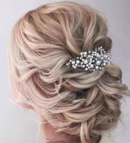 20 Chic Wedding Hair Updos For Elegant Brides Intended For Wavy Low Bun Bridal Hairstyles With Hair Accessory (View 18 of 25)